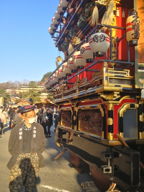 A proud local inspects his district's float during Takayama's  Sanno Matsuri, held April 14th and 15th of every year to offer prayers for the rice cultivating season. The parading of these centuries-old floats, adorned with gold, the finest lacquer finish and exquisite woodcarvings, is a highlight of the festivities.