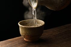 Warm sake poured from a ceramic bottle - designed to keep the liquid warm for the longest amount of time.